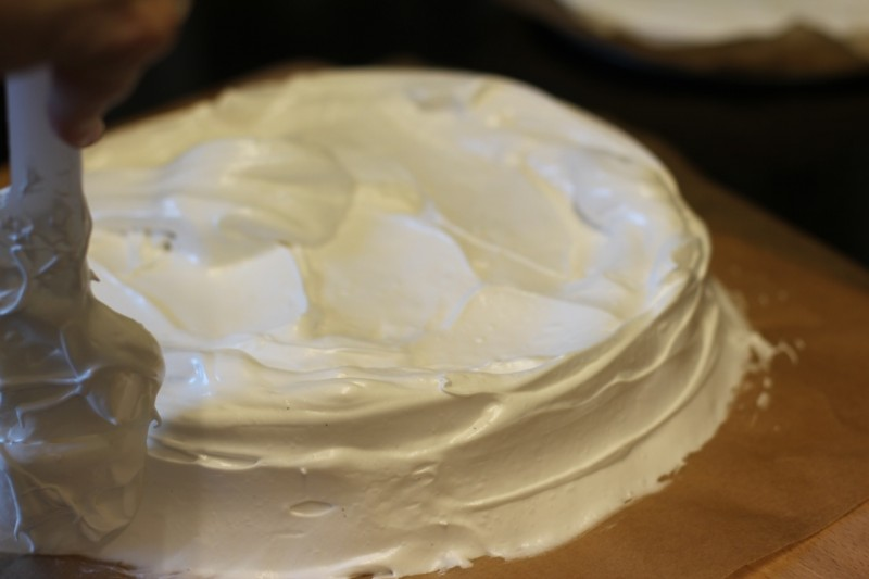 Covering the pavlova with its final layer of meringue.